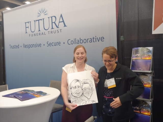 Women holding caricature at Gateway Center Collinsville during the Illinois Funeral Directors Association Conference