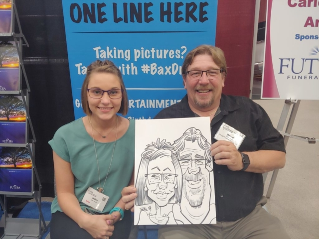 Father and Daughter holding caricature at Gateway Center Collinsville during the Illinois Funeral Directors Association Conference