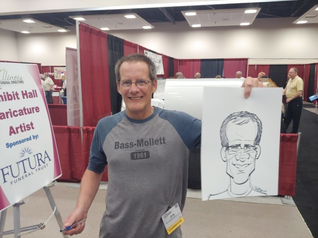 Man holding caricature at Gateway Center Collinsville during the Illinois Funeral Directors Association Conference