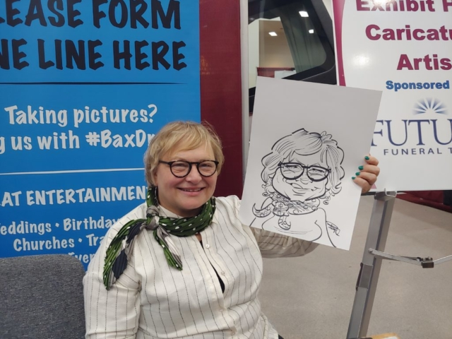 Woman holding caricature at Gateway Center Collinsville during the Illinois Funeral Directors Association Conference