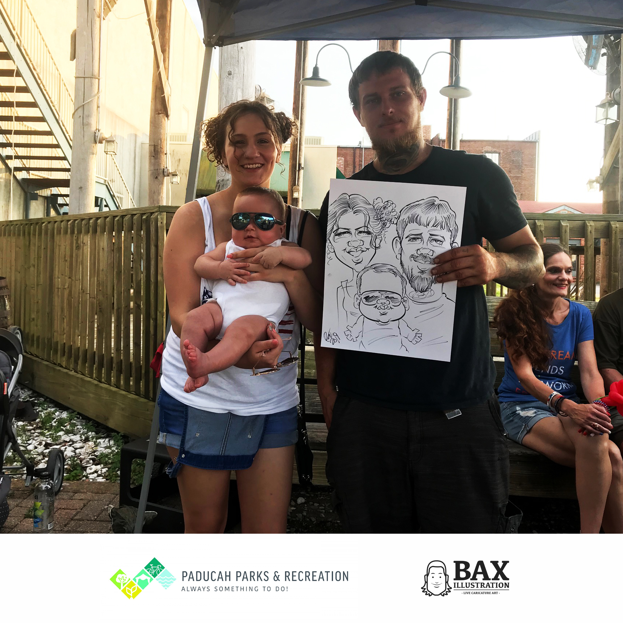 Couple holding baby and caricature by Bax Illustration in Paducah Kentucky at the 2019 Independence Day Celebration